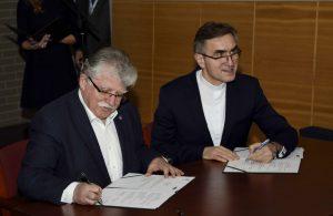 Na zdjęciu moment podpisania umowy pomiędzy KIGEiT (Stefan Kamiński) a UKSW (ks. Stanisław Dziekoński)